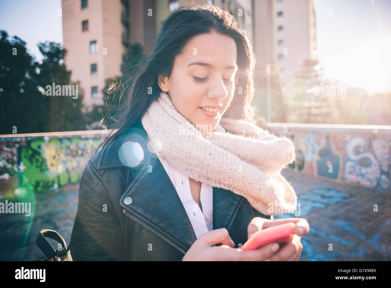 Half length of young beautiful long hair woman in city back light using smartphone tapping touchscreen smiling  - Stock Image