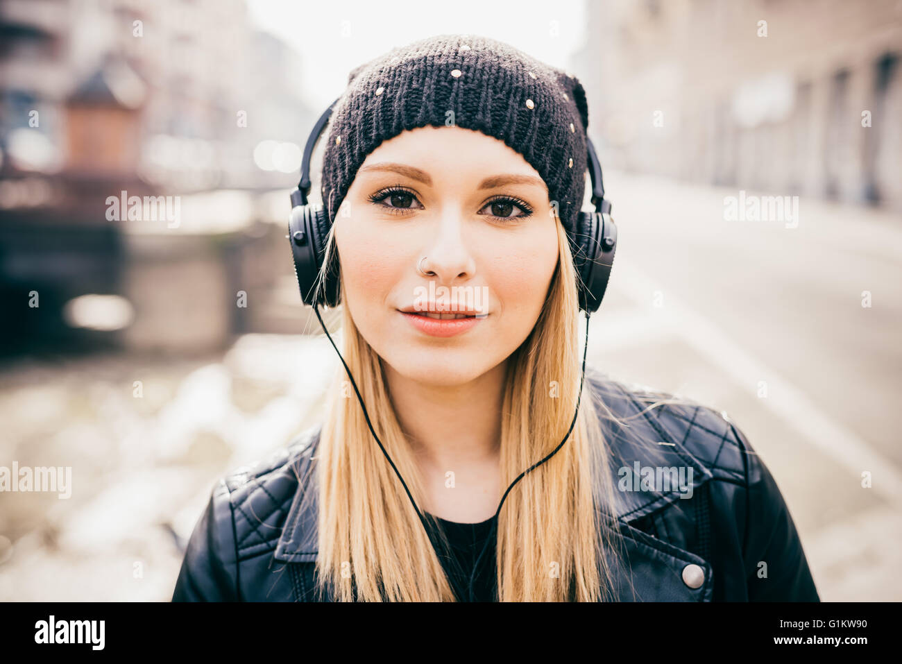 Half length of young beautiful blonde straight hair woman in the city with headphones listening to music, looking - Stock Image