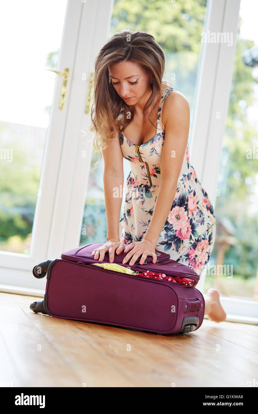Girl struggling to close suitcase - Stock Image