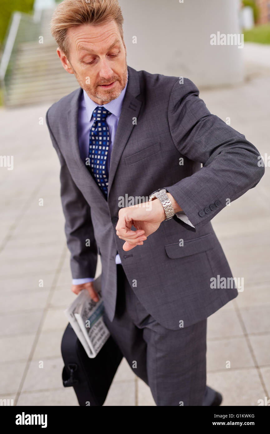 Man looking at his watch rushing to work - Stock Image