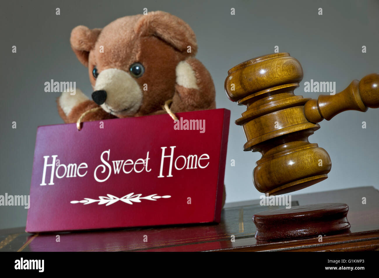 HOME SALE CONCEPT House sale by auction concept, auctioneers hammer & 'Home Sweet Home' sign  with child's - Stock Image