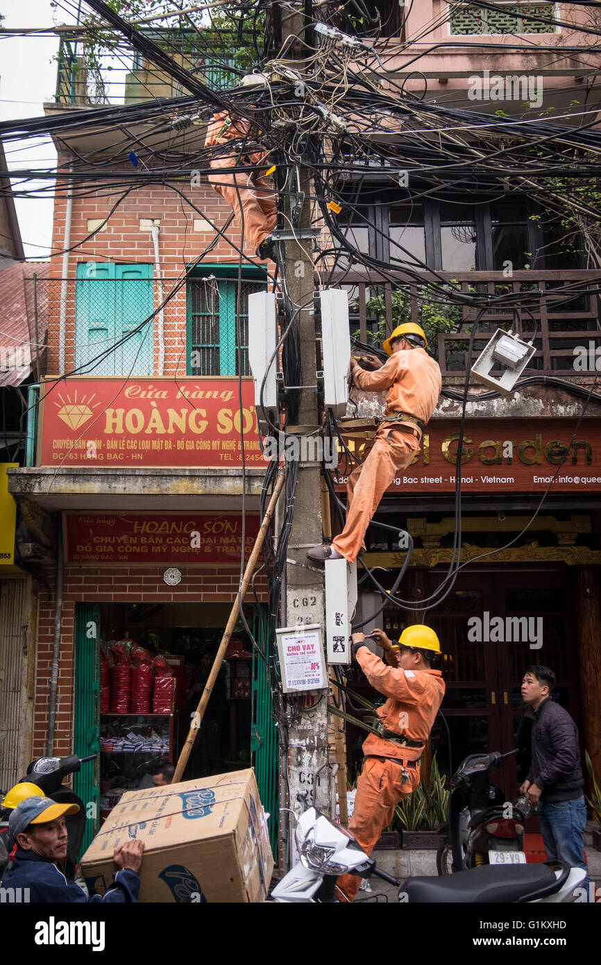 Men working on a telegraph pole in Hanoi's Old Quarter Stock Photo
