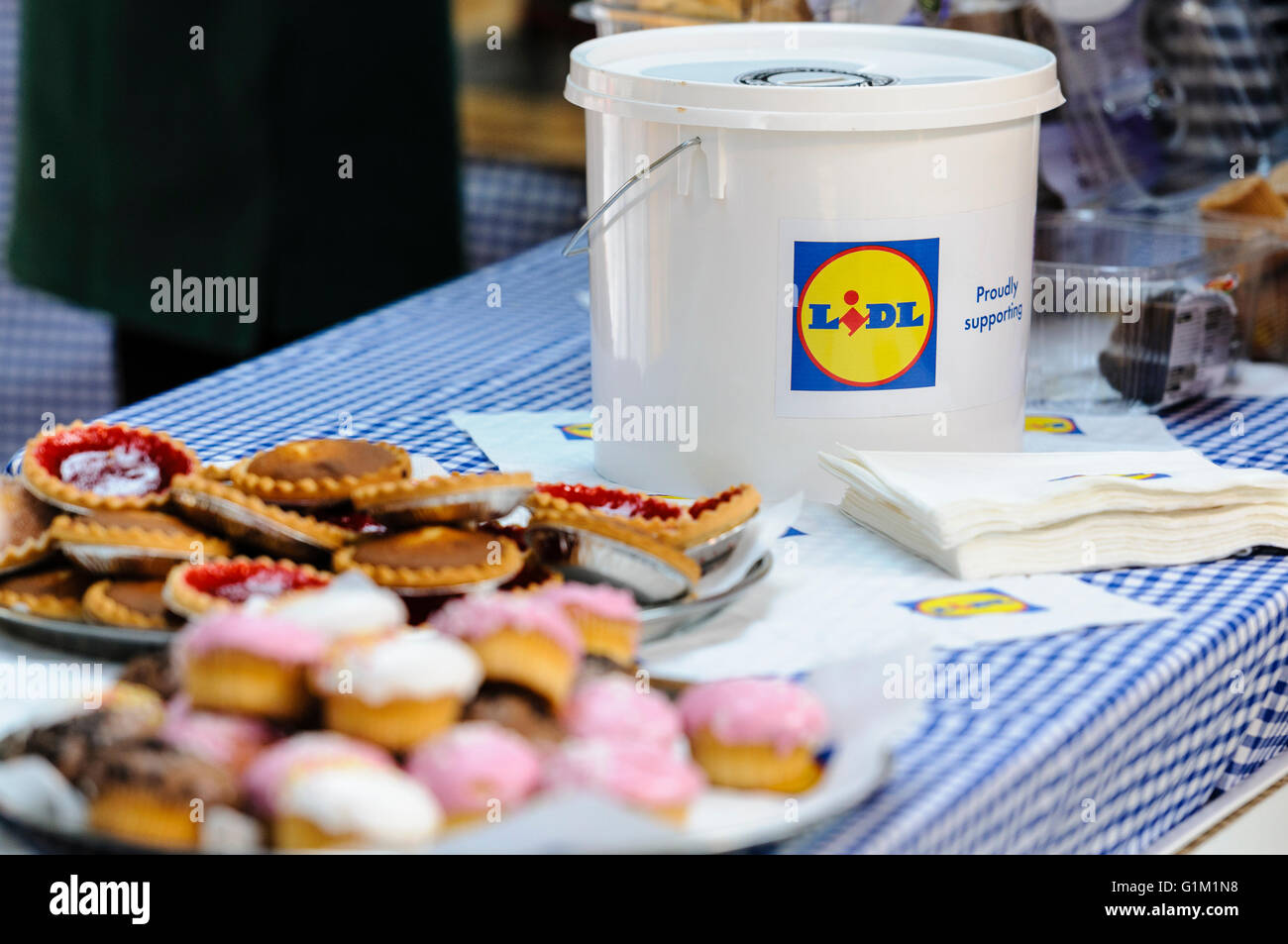 A charity collection box from Lidl on a table with buns Stock Photo