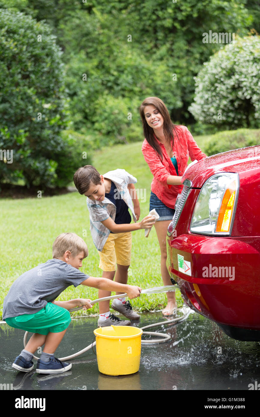 Woman with children washing car Stock Photo