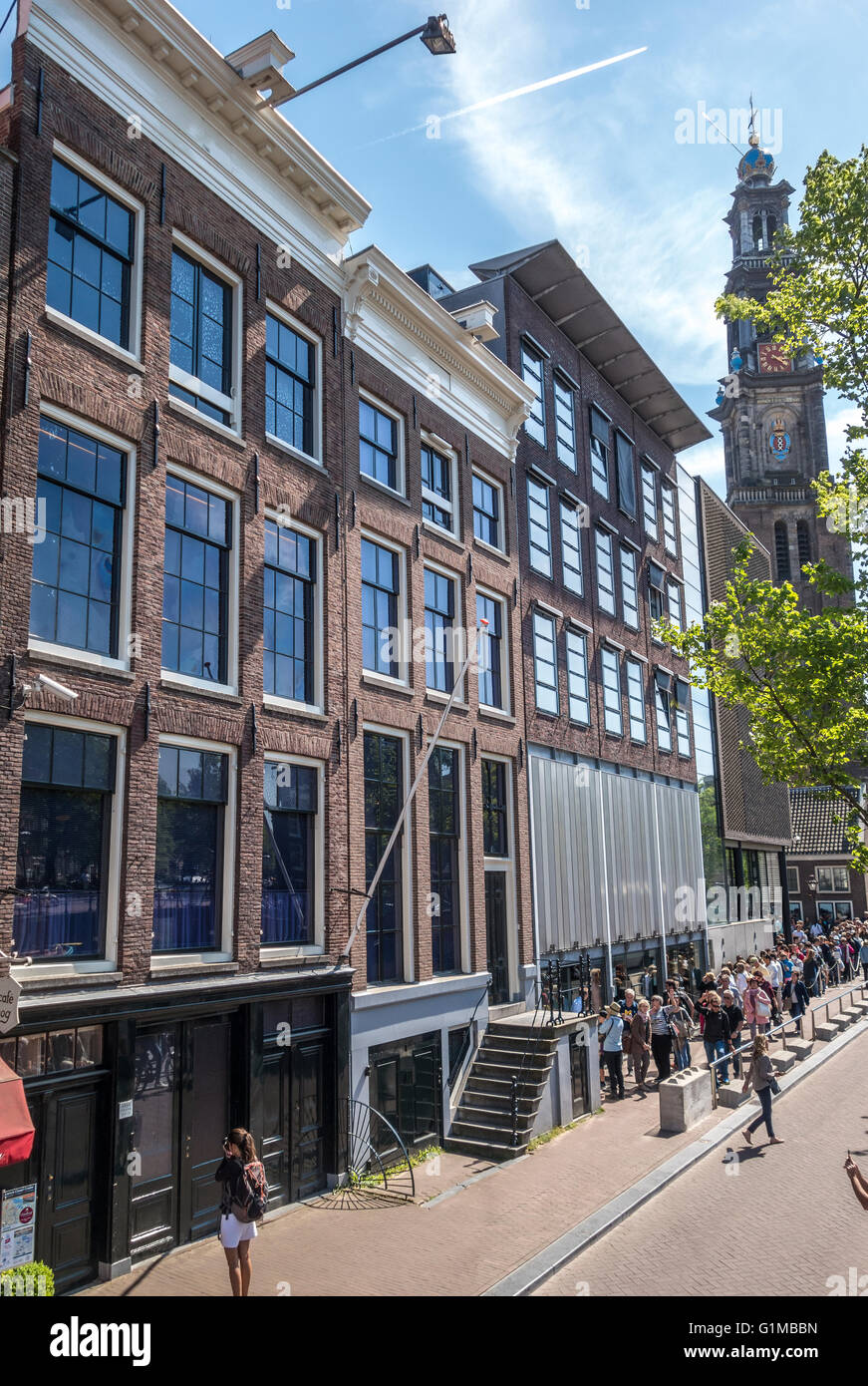 Anne Frank house and Anne Frank museum and entrance with tourists in lines. Amsterdam Prinsengracht Canal in Spring. - Stock Image