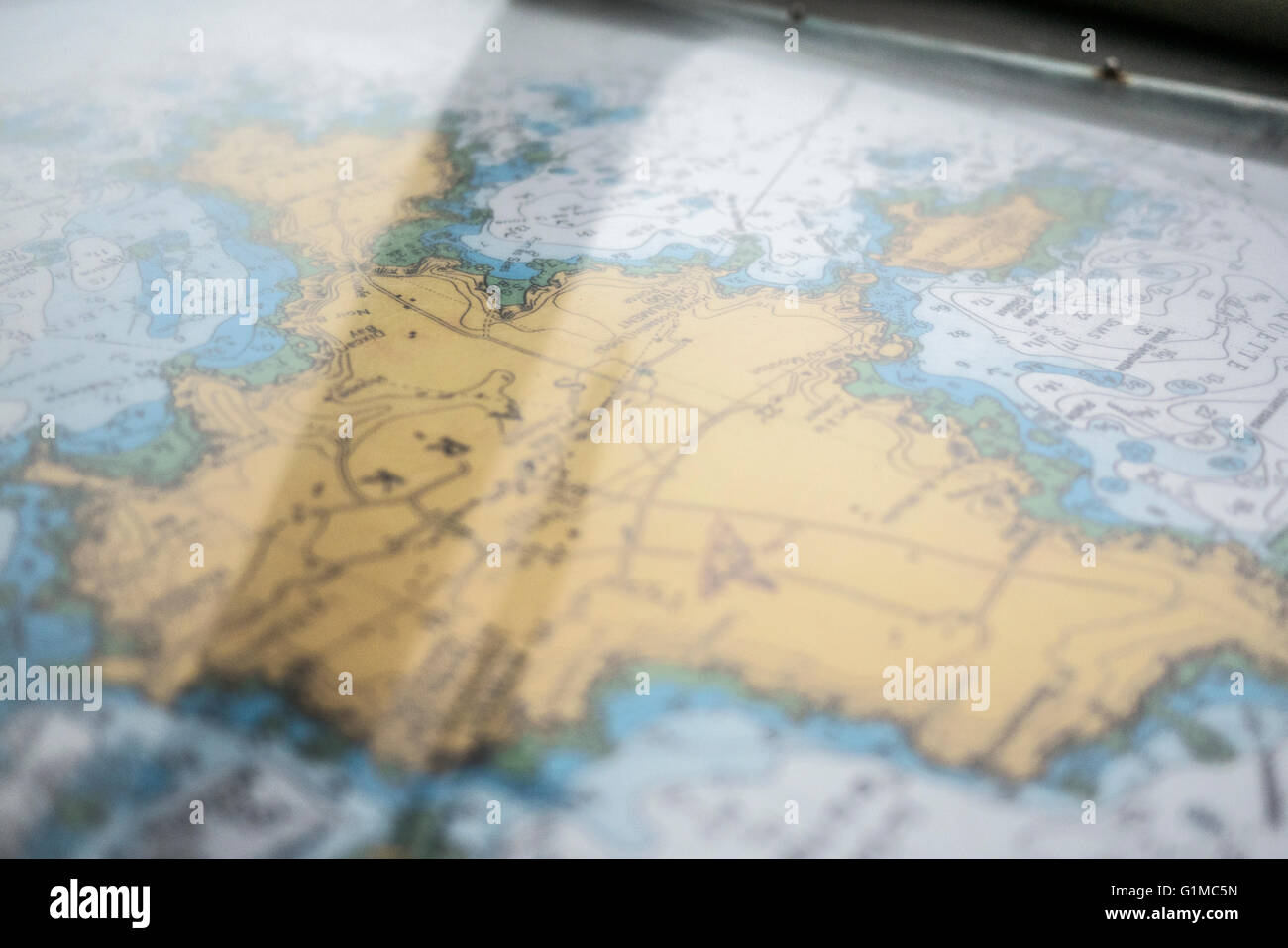 Close up photos of a shipping navigation map / chart of an island on a boat. - Stock Image