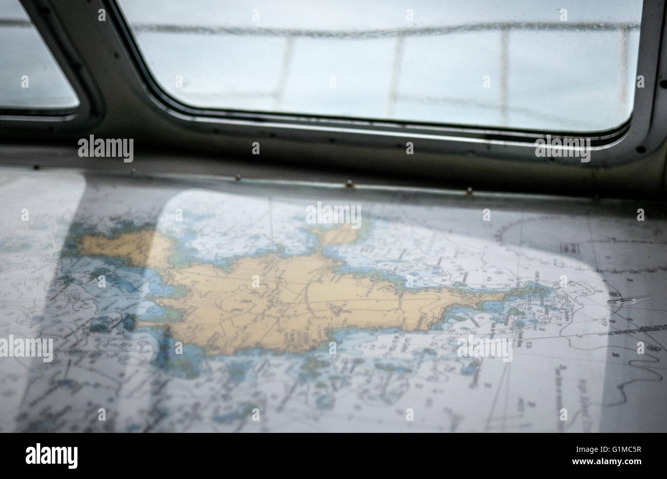 Close up photos of a shipping navigation map / chart of an island on a yacht sailing the sea. - Stock Image