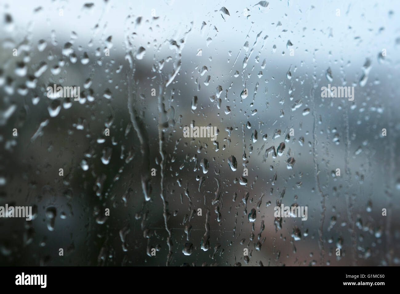 A close up of rain drops dripping down a window on a wet rainy day - Stock Image