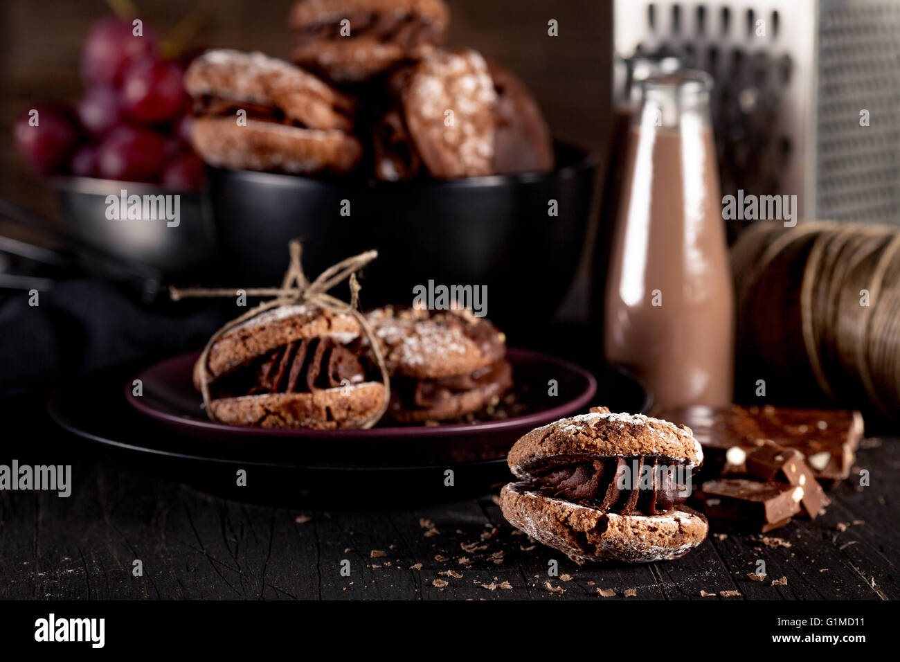 Italian maroni cookies on the plate and bowl with grapes, chocolate milkshakes, cloth, notebook on dark old wooden Stock Photo