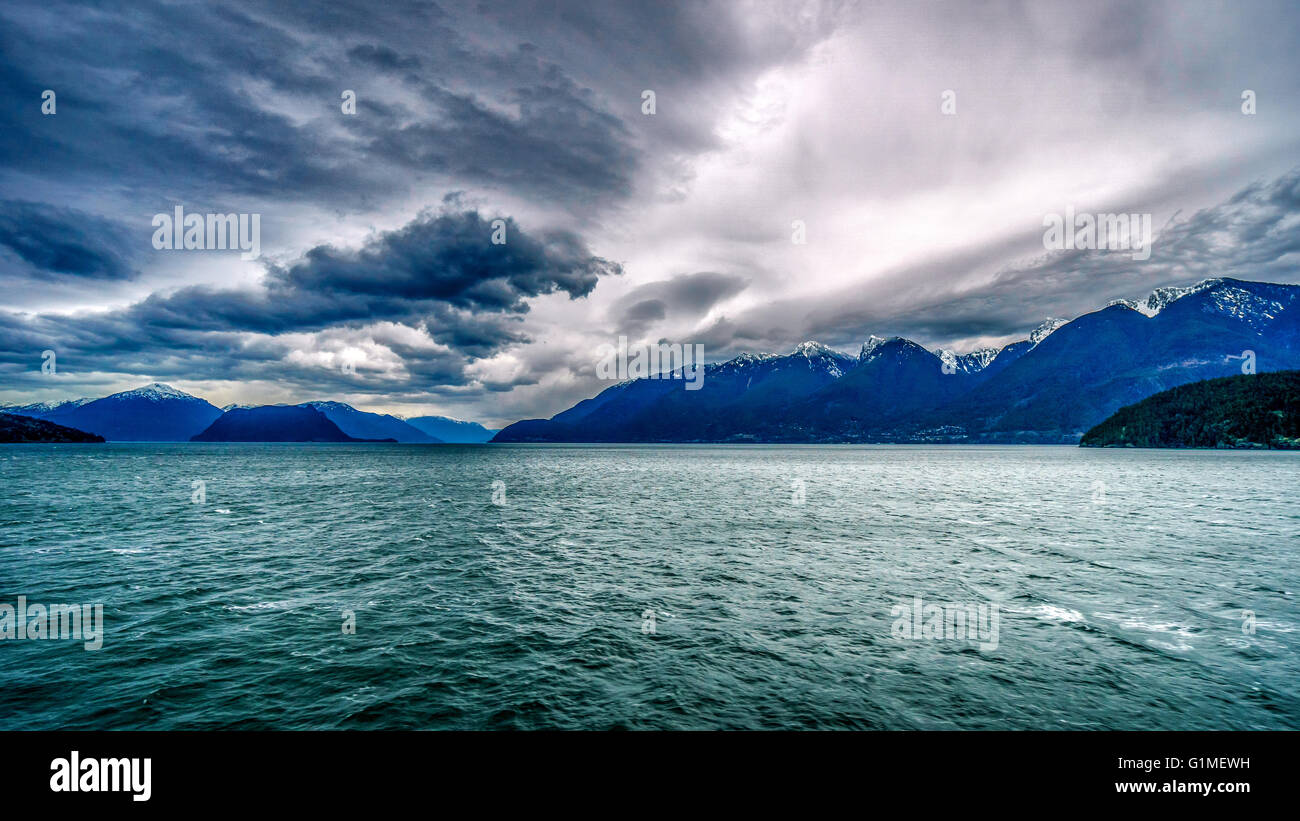 Early morning ferry ride from Horseshoe Bay to Sechelt in British Columbia Canada under threatening skies - Stock Image