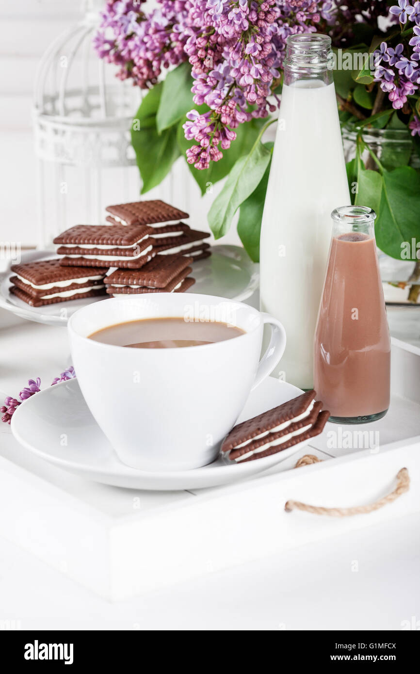 Cup of coffee and few bottles of milk and chocolate miklshakes on a white tray with lilac flowers on white shutters - Stock Image