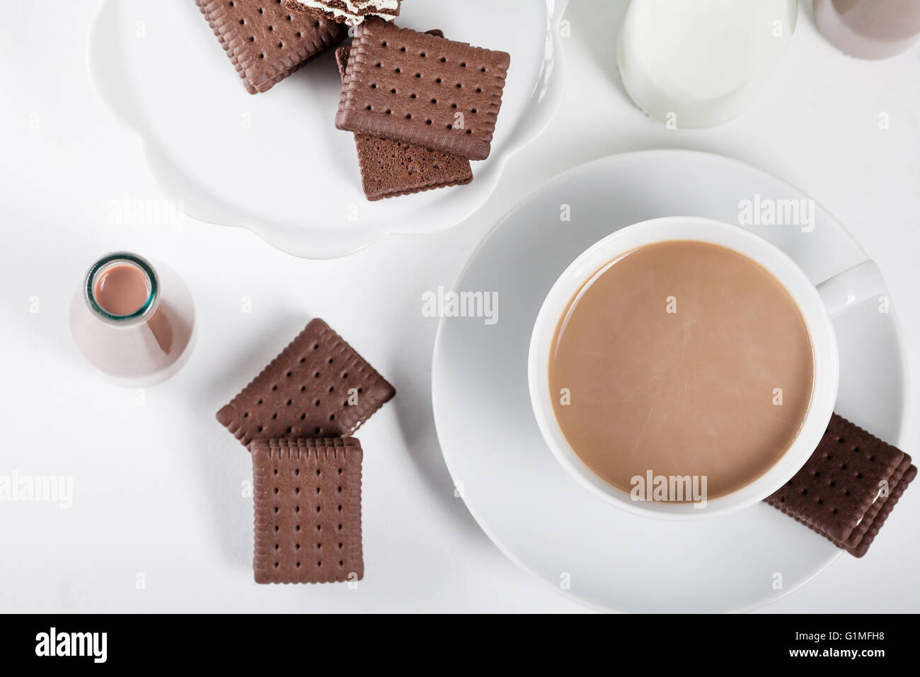 Cup of coffee and few bottles of milk and chocolate milkshakes on white background from the top - Stock Image