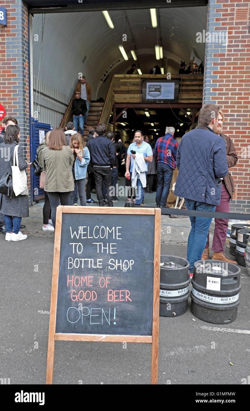 People outside craft beer outlet  'The Bottle Shop'  in Druid Street near Maltby Street Market, Ropewalk - Stock Image