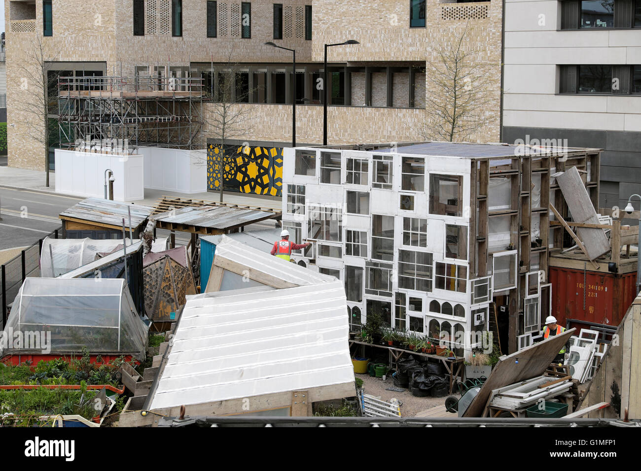 Men building structure from windows at the Skip Garden in Kings Cross London UK  KATHY DEWITT - Stock Image