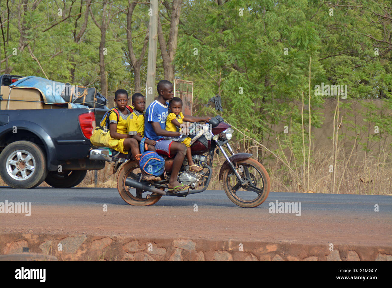 3 School kids in Ghana, being pick up with an small motorbike - Stock Image