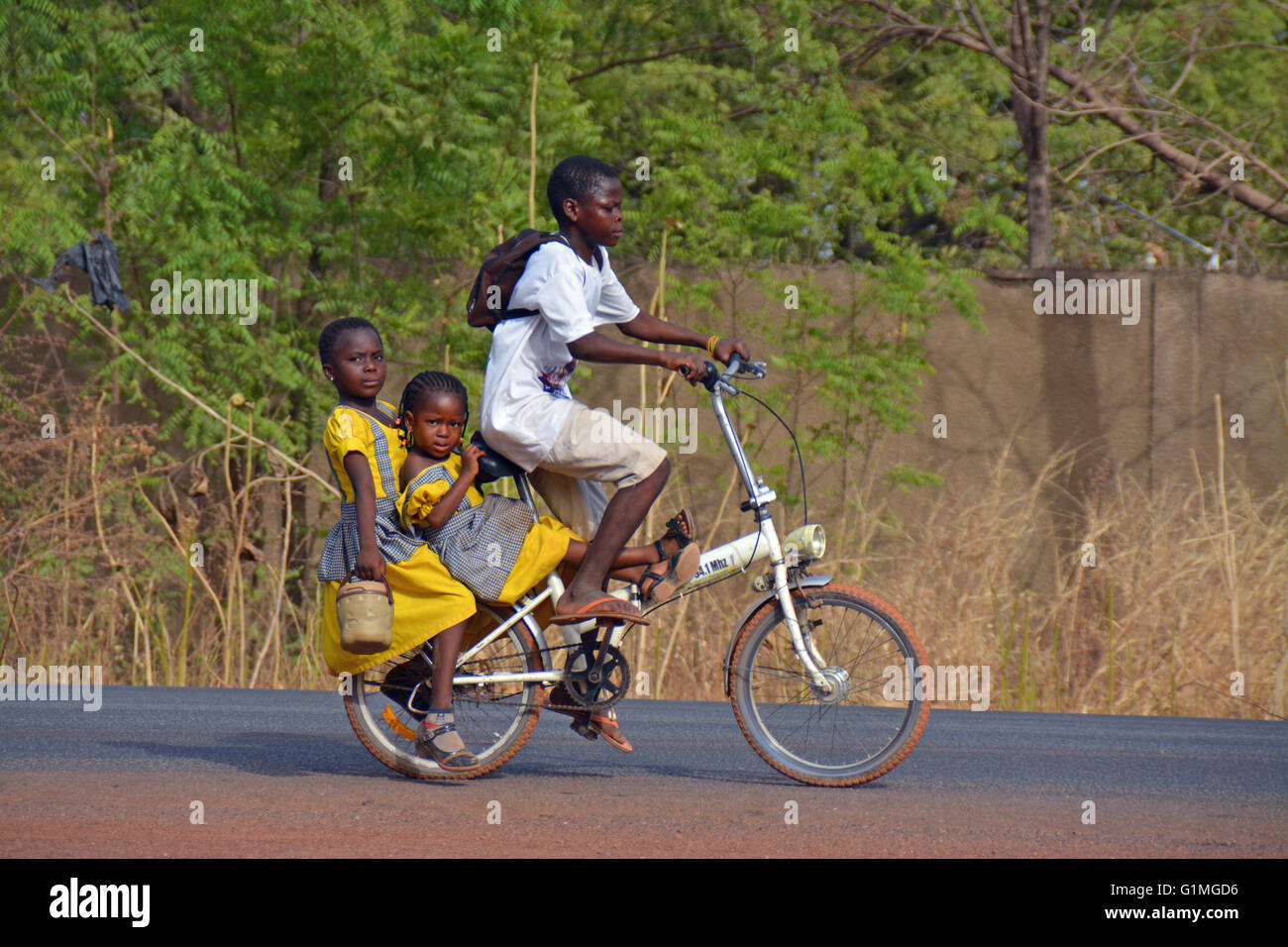 2 School kids in Ghana, being pick up with an small bicycle - Stock Image