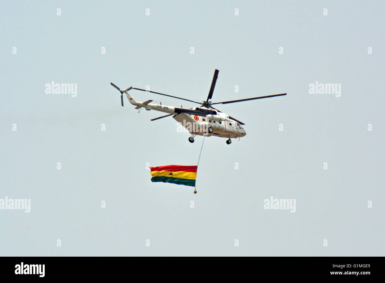 Ghana Air Force Helicopter, with attached Ghana Flag, overflying Accra at Independence Day celebrations. - Stock Image