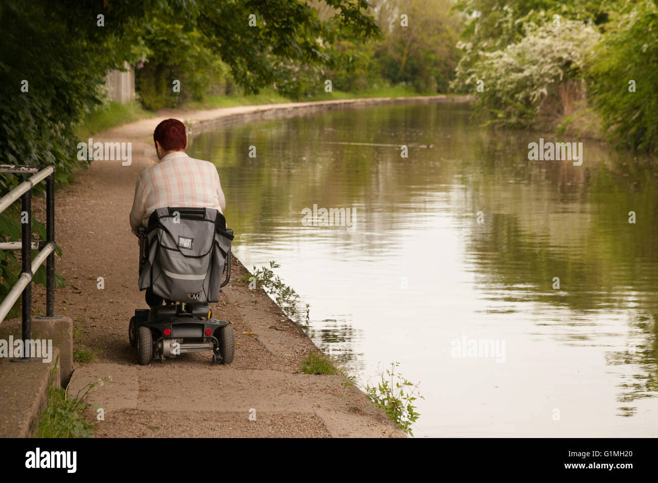 A disabled man using a disability scooter on the towpath, the Grand union Canal at Warwick, Warwickshire, UK - Stock Image