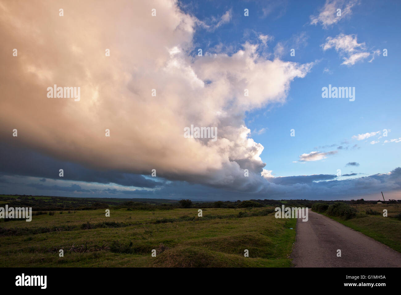 Huge cloud formation over Bodmin moor,blue sky with sunset yellow cloud above  moorland road runs parallel - Stock Image