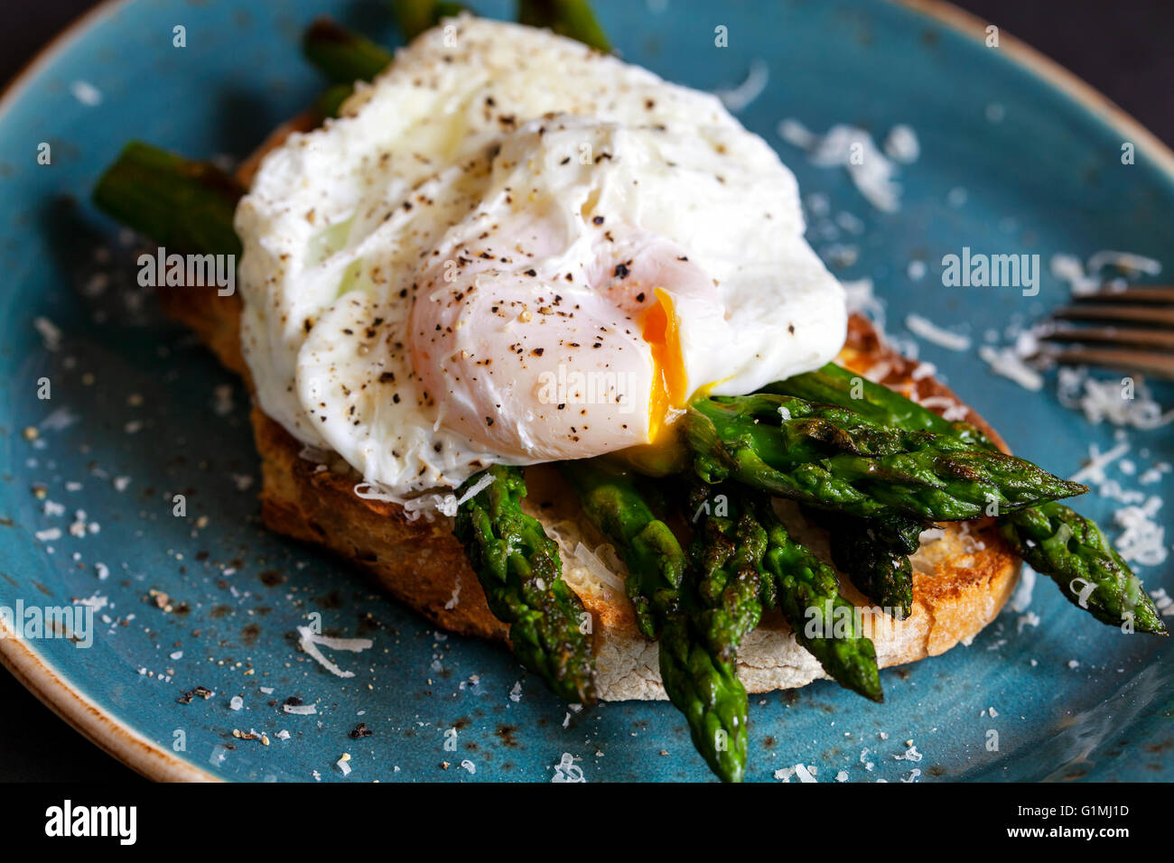 Toasted sourdough bread with grilled asparagus, poached egg and parmesan - Stock Image