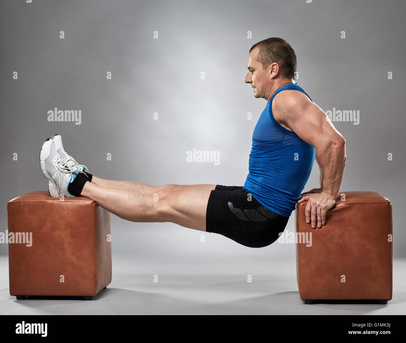 man doing pushup dips between two chairs in studio stock photo