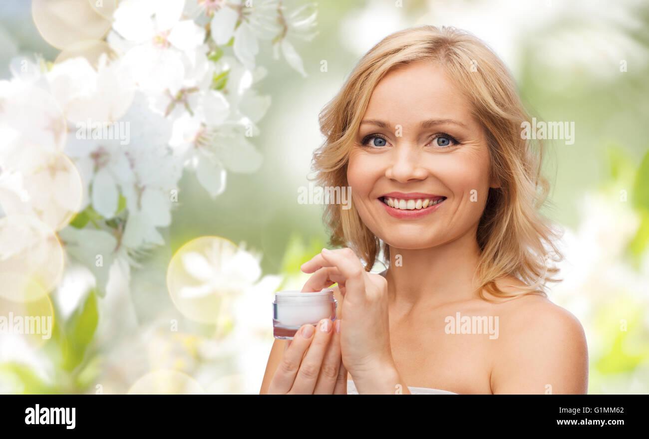 happy woman with cream jar - Stock Image