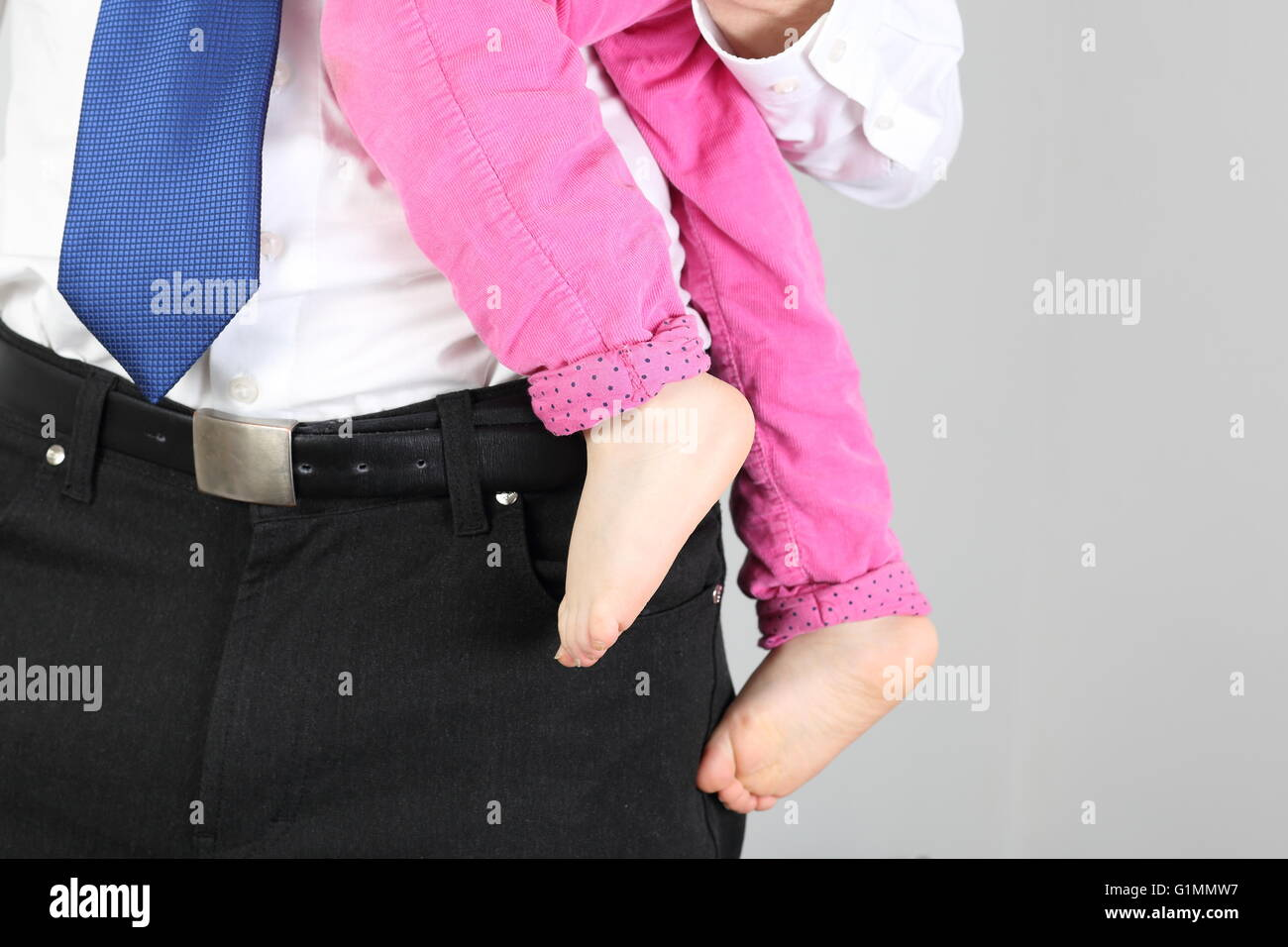 Businessman with child on arm - Stock Image