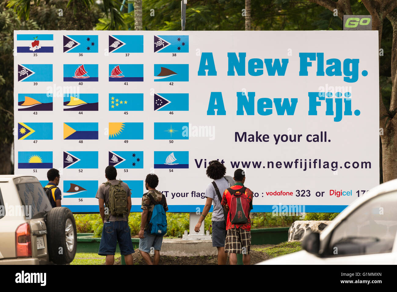 Young men look at a roadside poster in Suva showing different designs  for a new national flag for Fiji. Designs - Stock Image