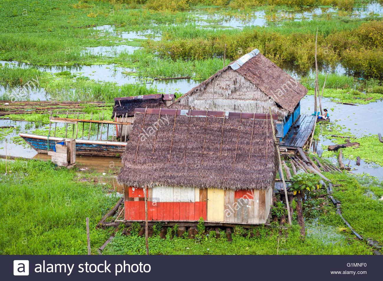A woman washing clothes behind her house along Rio Itaya, Iquitos, Loreto, Peru - Stock Image