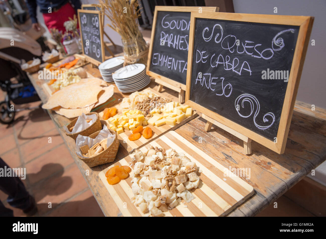 Several kinds of cheese served on vintage wooden table and blackboards written in spanish - Stock Image