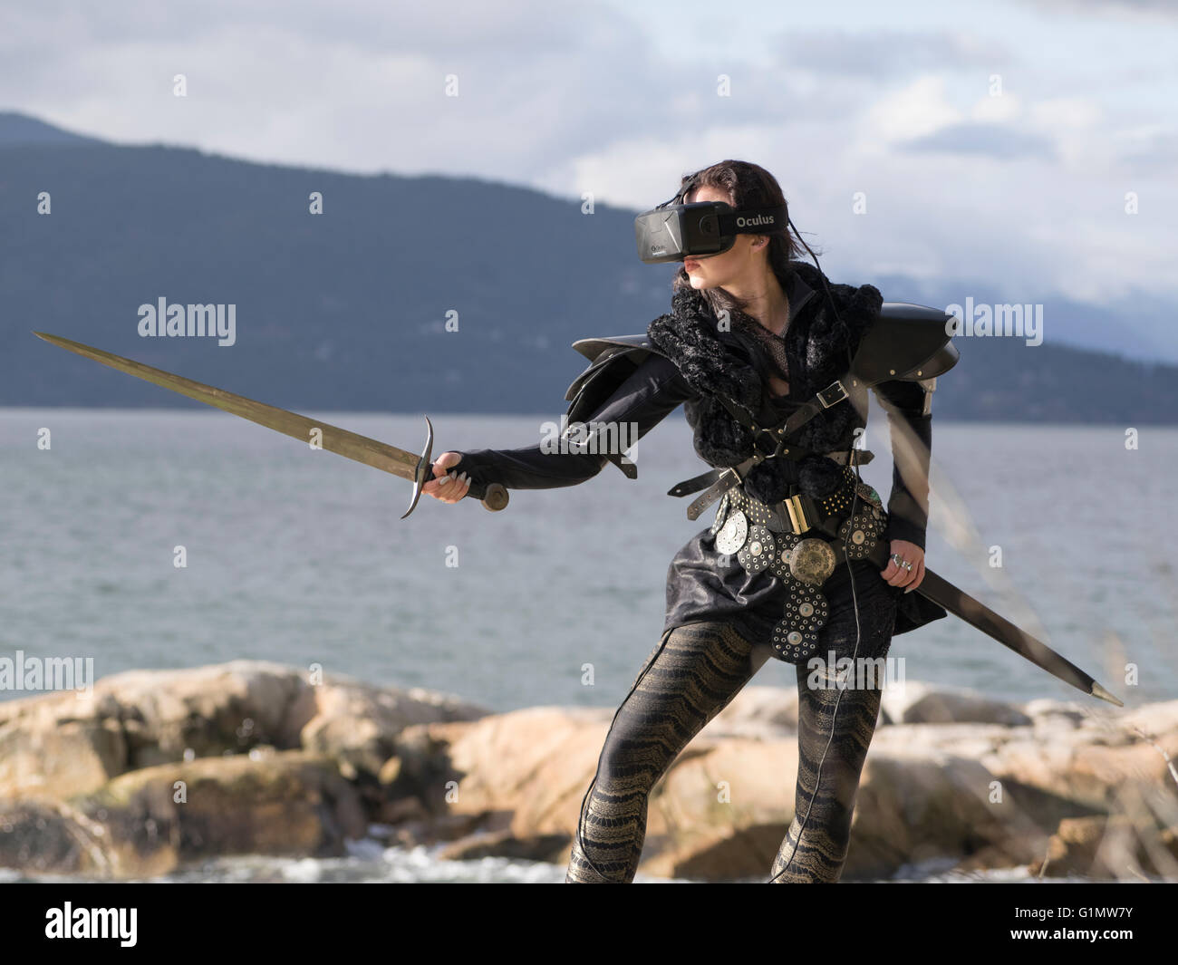Conceptual picture of a young woman wearing costume and Oculus Rift Virtual Reality headset - Stock Image