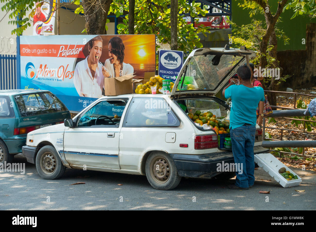 A street vendor selling fresh fruit from the trunk of his car. Quepos, Puntarenas Provice, Costa Rica. Stock Photo
