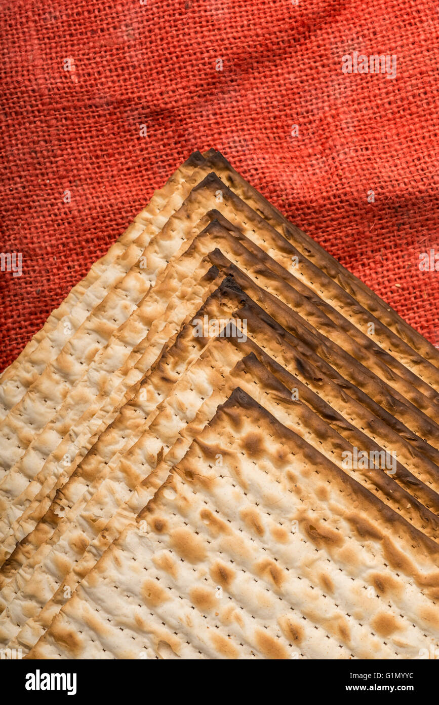 Matzah - jewish passover bread on red burlap - Stock Image