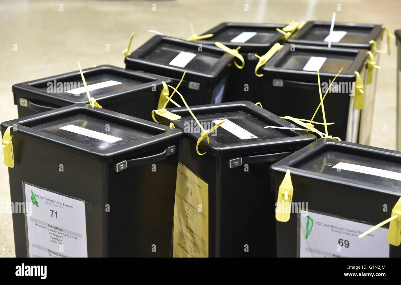 Election count, Ballot boxes, black with yellow tags, unopened,in a line on the ground, from the top, sitting on - Stock Image