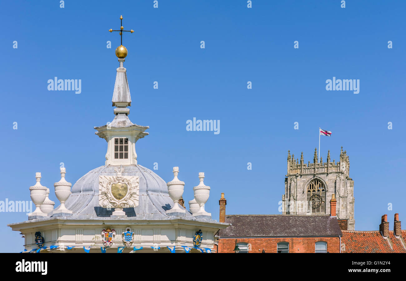 The ornate top of the bandstand, rooftops, and part of St Mary's church with flag of St George flying against - Stock Image