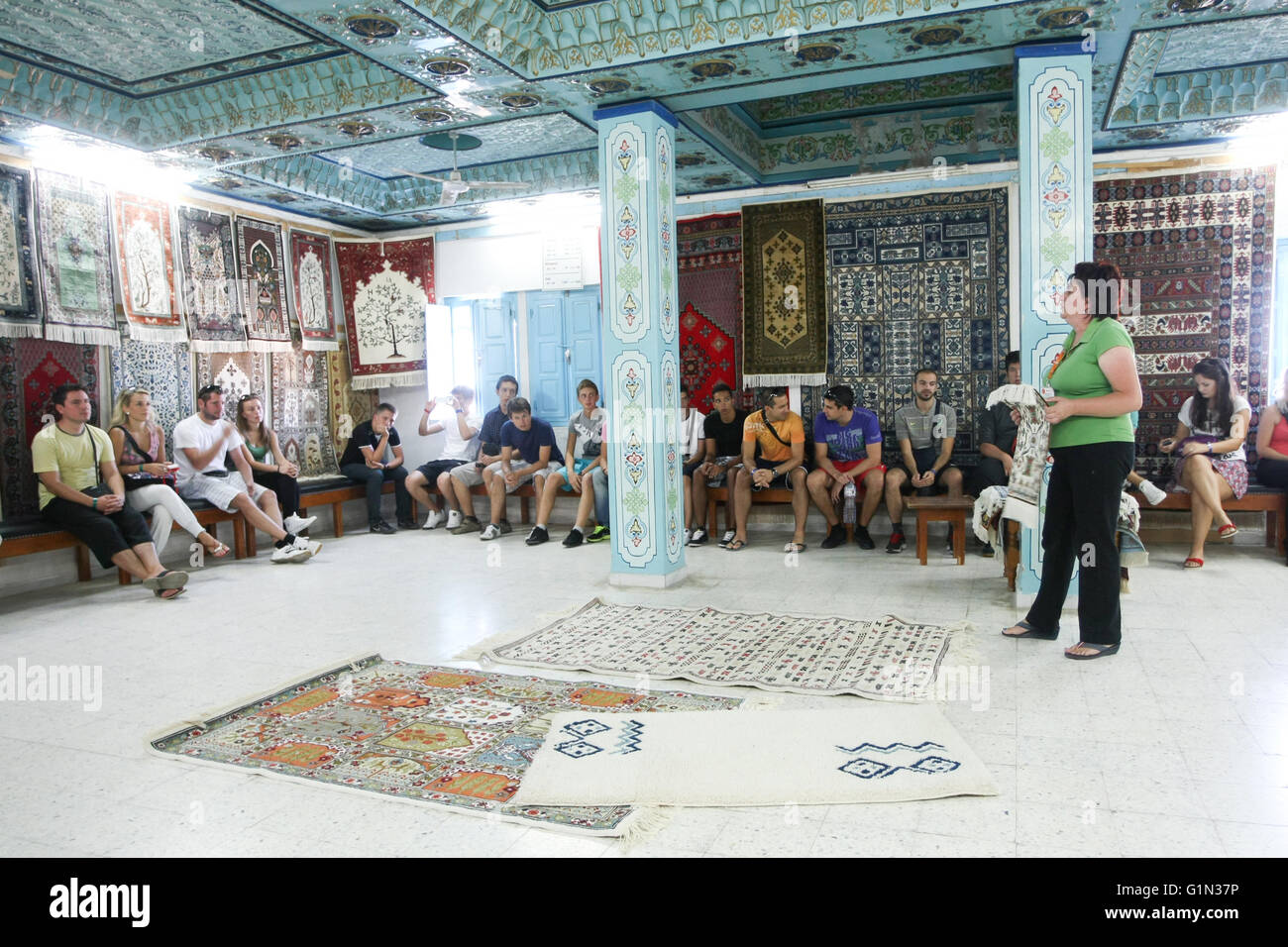 Tourist group listening to the tourist guide in an ancient shop with old craft production of silk and wool in Kairouan, Stock Photo