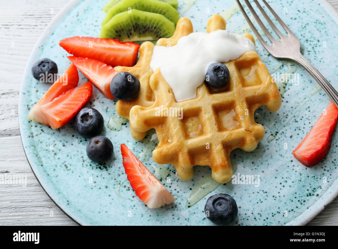waffles with yogurt and fresh berries on plate - Stock Image