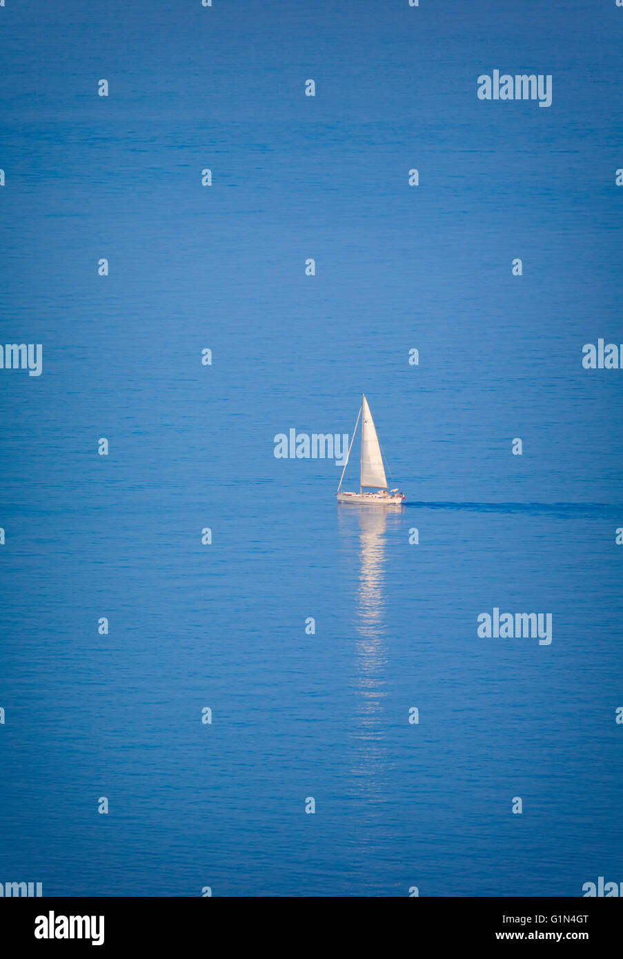 Lone yacht sailing off Riviera dei Fiori, the Coast of Flowers, Imperia Province, Liguria, Italy. - Stock Image