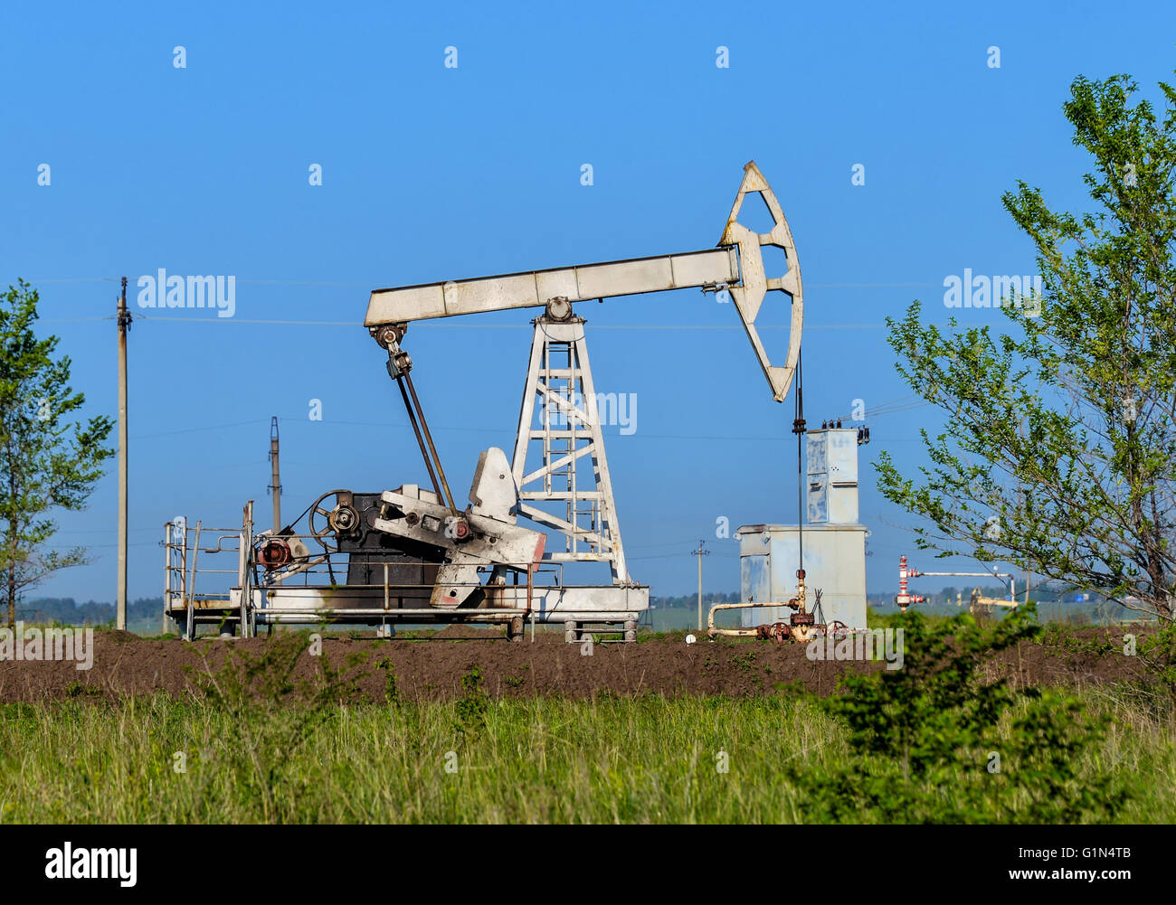 Old oil pumpjack on the summer field - Stock Image