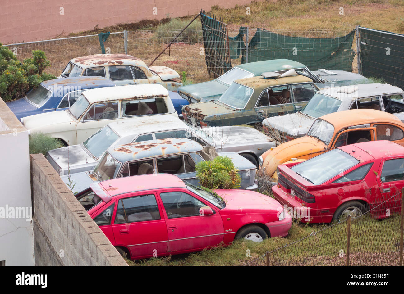 Rusting old cars in compound behind large house in Spain - Stock Image