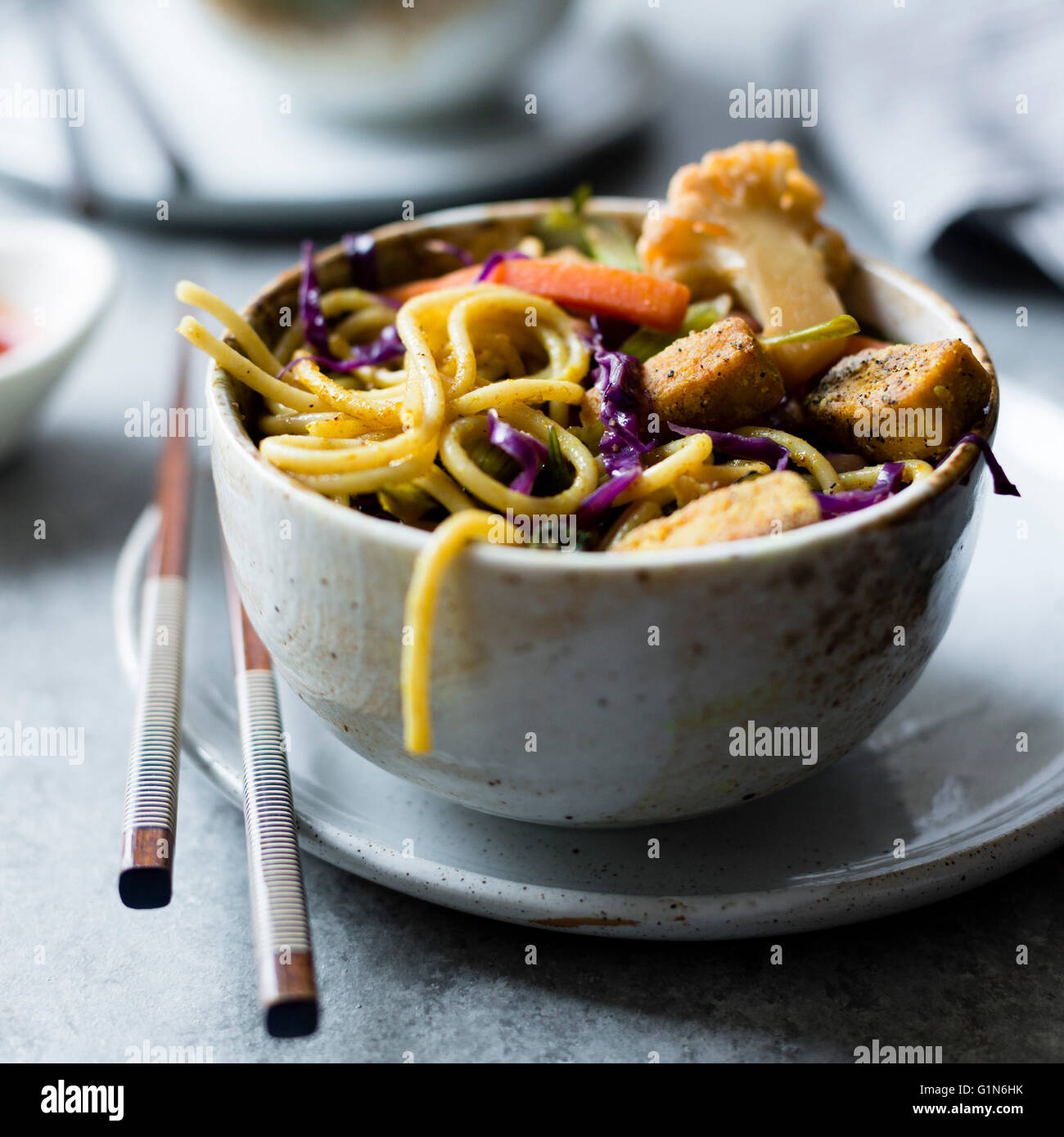 Curried noodles with crispy tofu & winter vegetables, gluten-free and vegan. Stock Photo