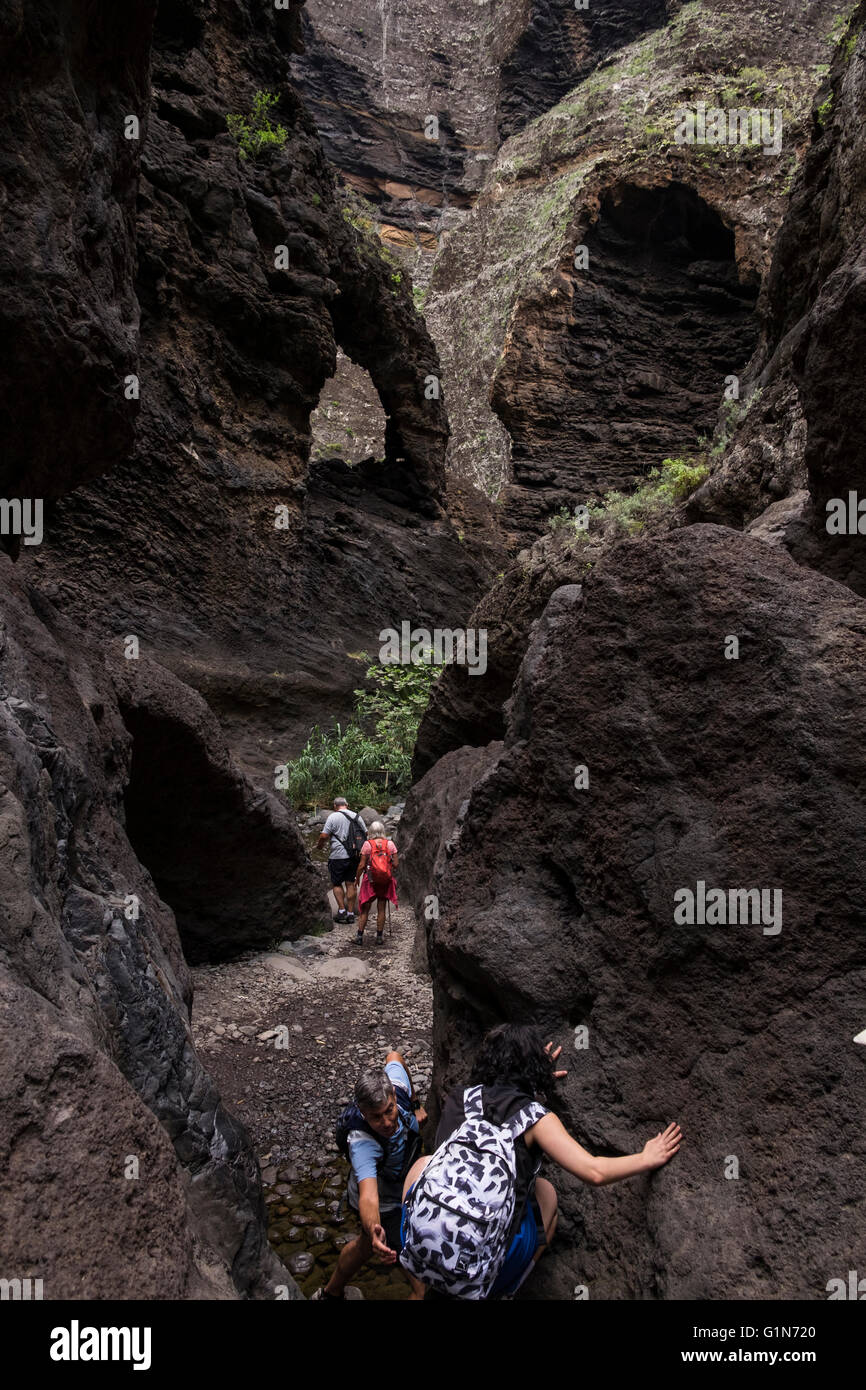 Walkers on the pathway through the Masca barranco, Tenerife, Canary Islands, Spain. - Stock Image