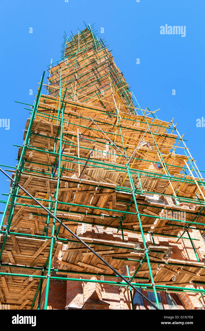 The spire of the Catholic Church in scaffolding against the blue sky - Stock Image