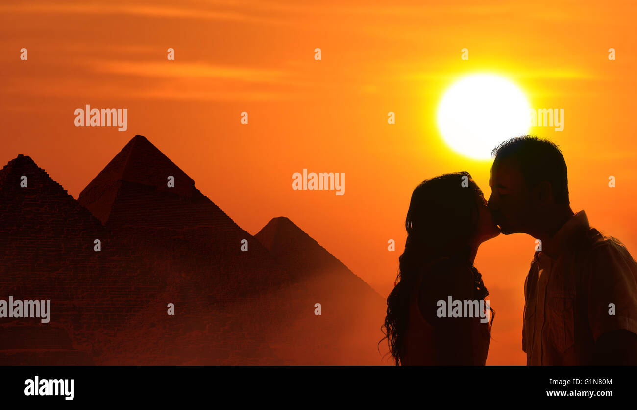 Backlit loving couple honeymoon in Egypt with pyramids and sunset background - Stock Image