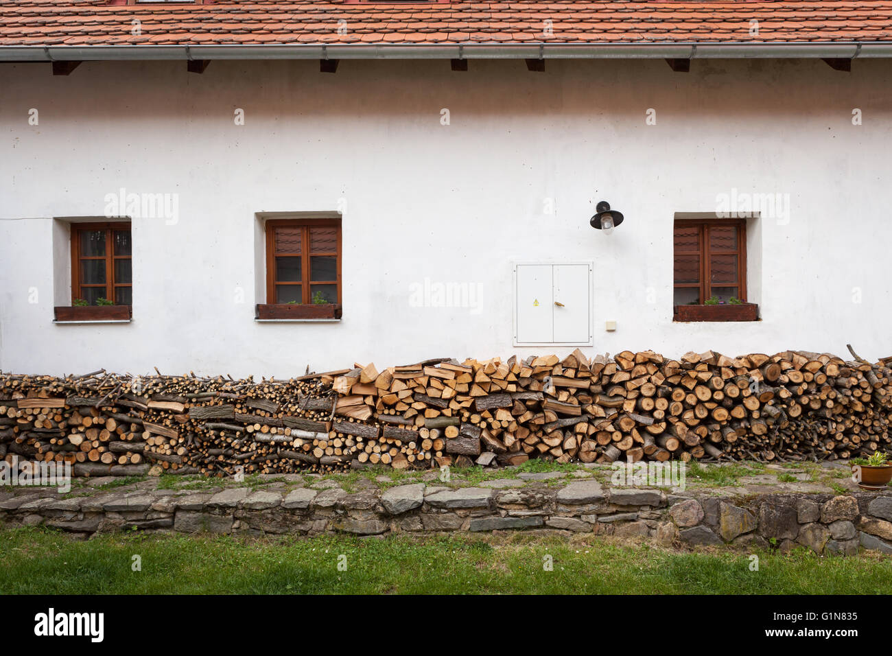 Chopped firewood piles against the side of a rural building - Stock Image