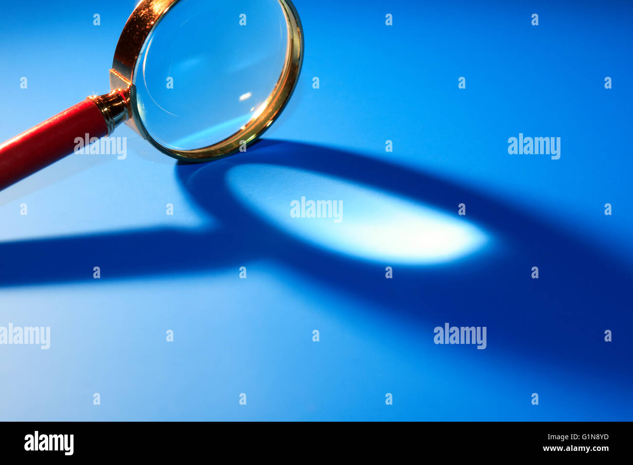 Magnifying glass with long shadow on blue background - Stock Image