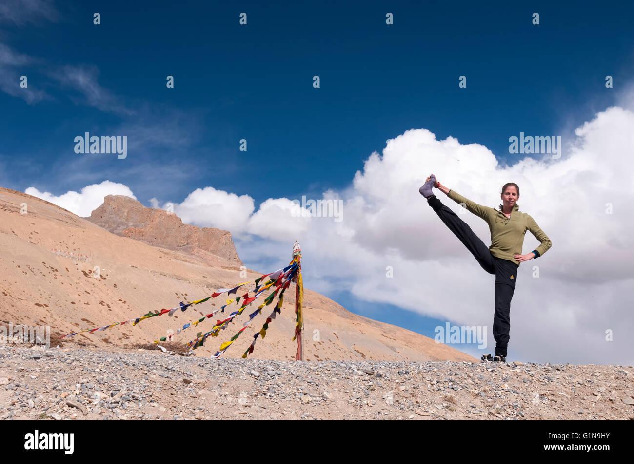 Young female practising yoga pose Utthita hasta padangusthasana in mountains - Stock Image