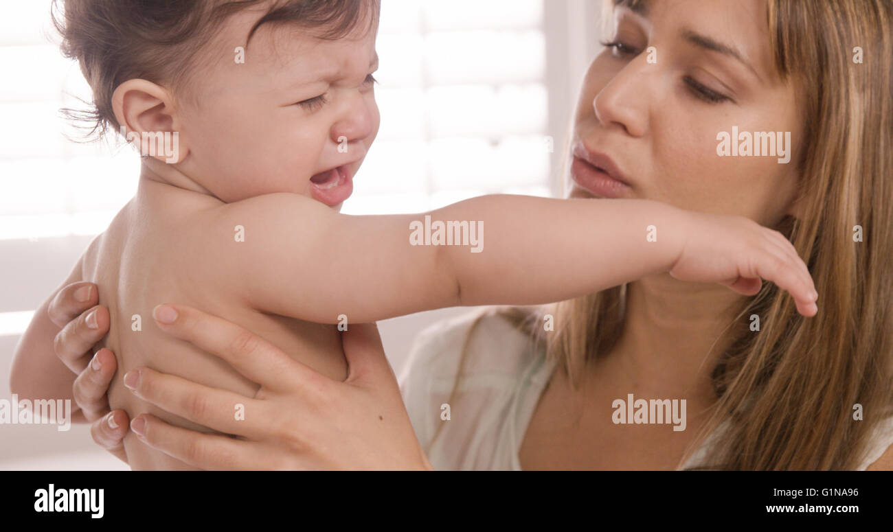 Mother carrying her baby crying - Stock Image