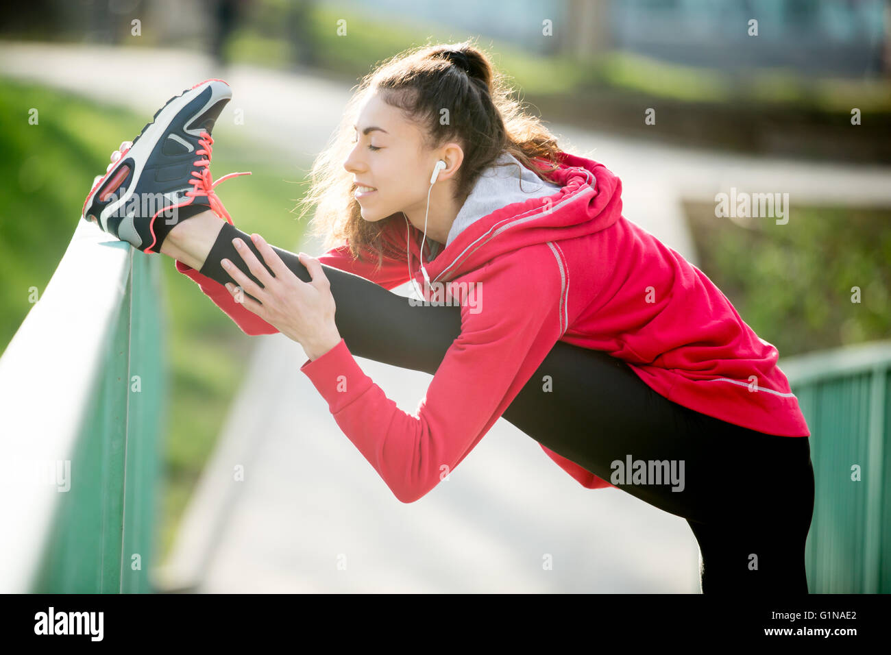 Profile portrait of sporty woman doing hamstring stretch in park after jogging. Female athlete runner getting ready - Stock Image
