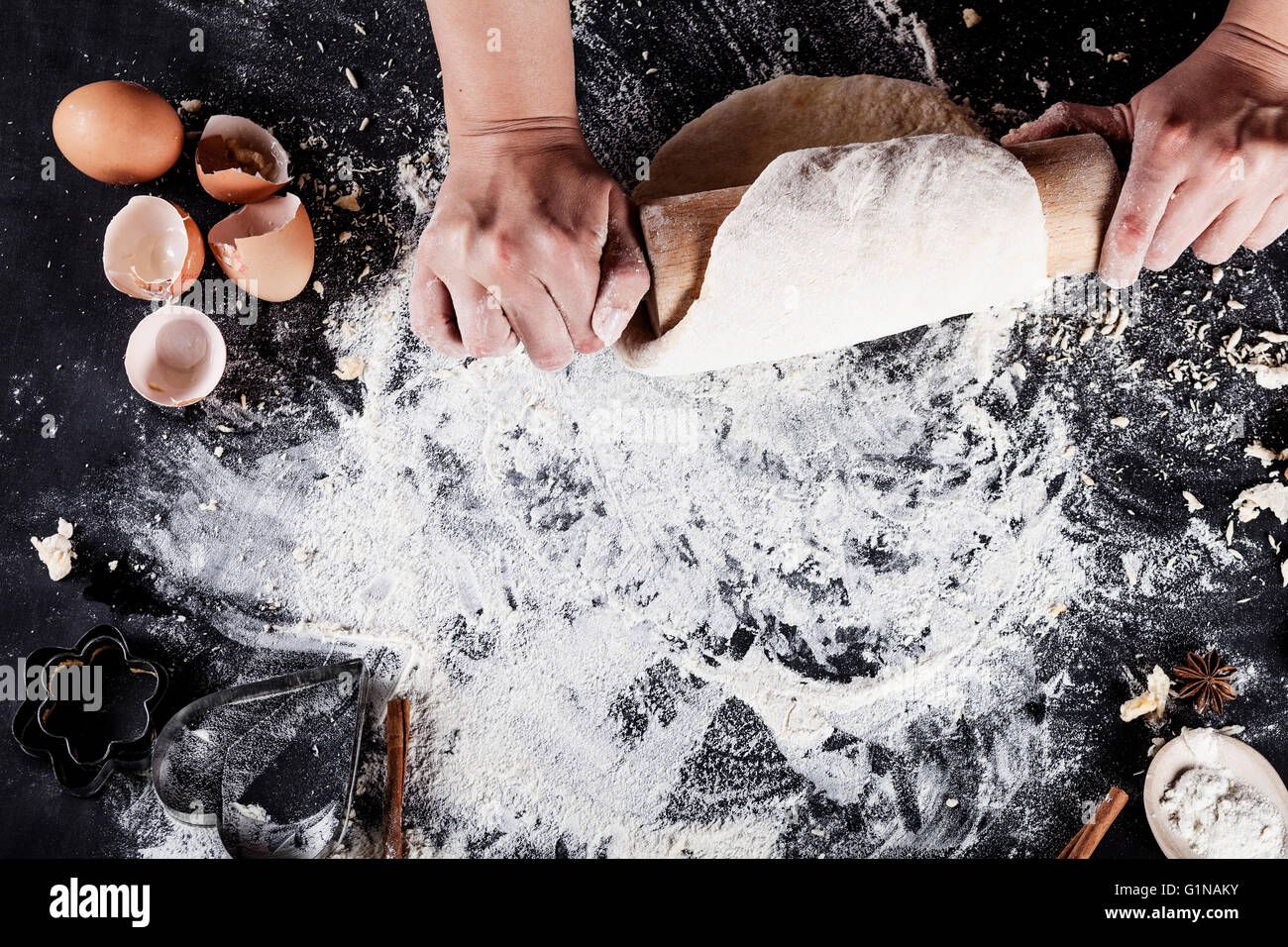 Making of cookies with ingredients like eggs, flour, cinnamon, anise, rolling pin, paper on blackboard from the Stock Photo